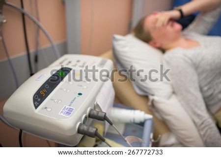 inspecting fetal monitor report with expecting mother in labor pain - stock photo