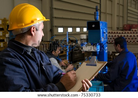 Inspector checking workers equipment motion blurred - a series of INDUSTRIAL images. - stock photo