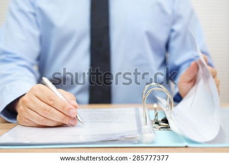inspector is  reviewing invoices in binder - stock photo