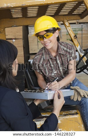 Inspector taking sign on document from female warehouse worker - stock photo