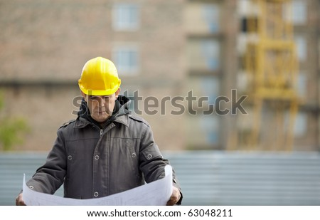 Inspector with blueprints on construction site, natural light, focus on foreground - stock photo