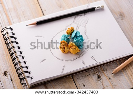 Inspiration concept crumpled paper with light bulb metaphor for good idea - stock photo