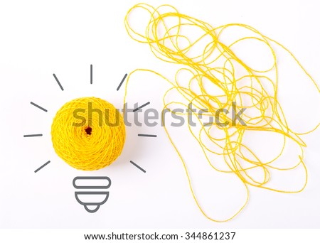 Inspiration concept yarn yellow light bulb metaphor for good idea. Symbol of idea as light bulb on sheet of paper from skein of thread, isolated on white - stock photo