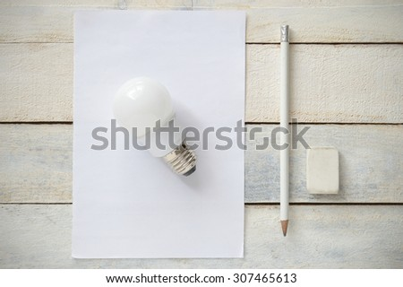 Inspirational image representing the simplicity of a good idea. A bulb on a white blank paper next to a white pen and a rubber. All the stuff on a white wooden table. Top view. - stock photo