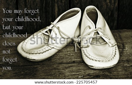 Inspirational quote about childhood by Michael Dibdin with a closeup of vintage baby shoes on a grunge wood backdrop. - stock photo