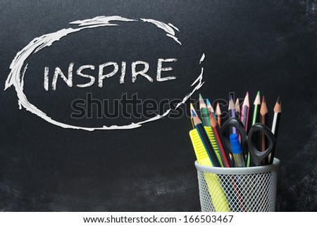 Inspire handwritten with white chalk on a blackboard.Office tools - stock photo