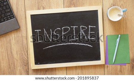 Inspire written on a chalkboard at the office - stock photo