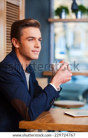 Inspired by cup of fresh coffee. Side view of handsome young man enjoying coffee in cafe while sitting at the table with digital tablet laying near him  - stock photo