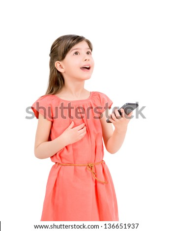 Inspired cute little girl in red dress looking up and holding in her hand mobile phone. Isolated on white background. - stock photo