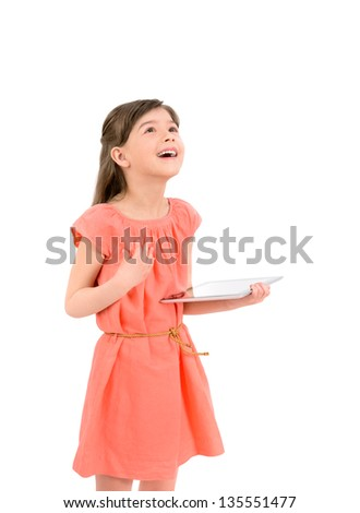 Inspired happy young girl in red dress looking up on copyspace and holding in her hand digital tablet. Isolated on white background. - stock photo