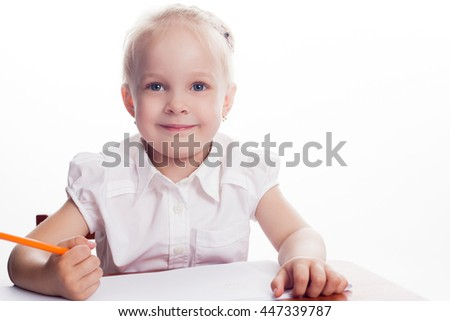 Inspired little girl at the table draw with pencils, isolated on white background - stock photo