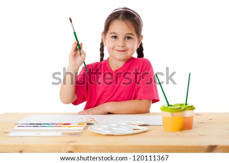 Inspired little girl with paintbrush and watercolors at the table, isolated on white - stock photo