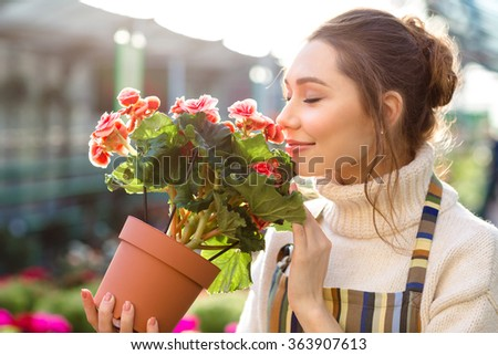 Inspired smiling young woman florist smelling flowers of begonia in greenhouse  - stock photo