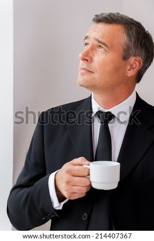 Inspired with cup of fresh coffee. Thoughtful mature man in formalwear holding coffee cup and looking away while standing near window - stock photo