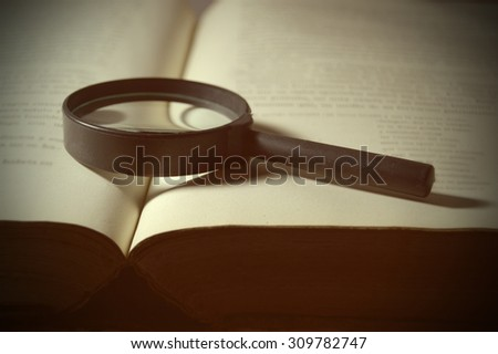 Inspiring scene with a magnifying glass on an open old book representing historical investigations. Romantic reading of the classic books. Blank copy space for the editor's text. - stock photo
