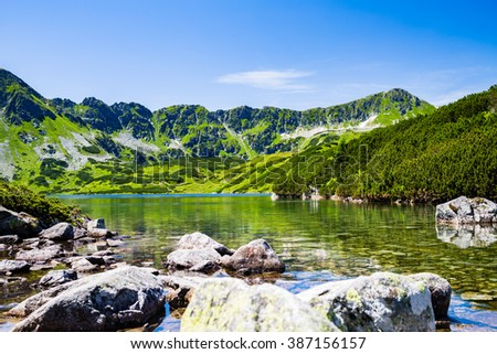 Inspiring Tatra Mountains Landscape View, sunny day in summer Tatras. Looking at clear pond in green valley from mountain ridge over blue sunny sky, Poland in Europe - stock photo