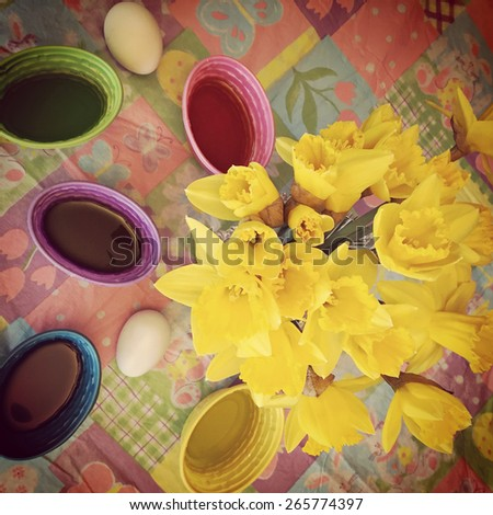 instagram closeup of daffodils and Easter eggs dye on table - stock photo