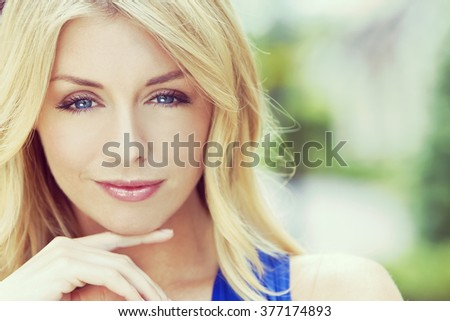 Instagram filter style portrait of naturally beautiful woman in her twenties with blond hair and blue eyes, shot outside in natural sunlight - stock photo