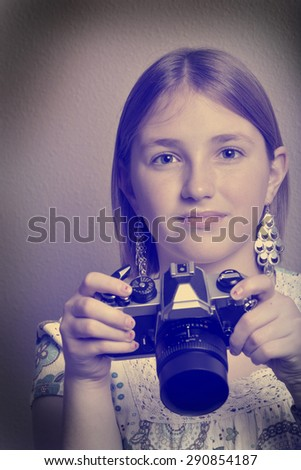 Instagram portrait of young girl teenager photographer holding vintage old camera shooting photographs - stock photo