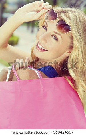 Instagram style photograph of beautiful, happy and fashionable young blond woman with heart shaped sunglasses and colorful shopping bags over her shoulder. - stock photo