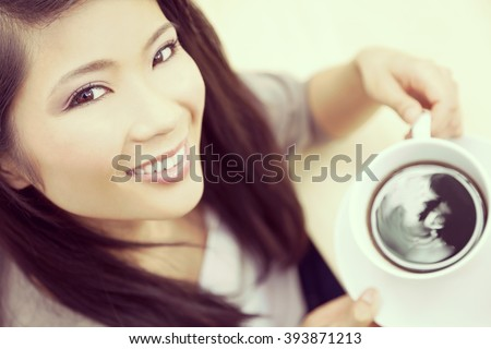 Instagram style portrait of beautiful young Chinese Asian woman with perfect teeth smiling drinking tea or coffee from a white cup and saucer - stock photo