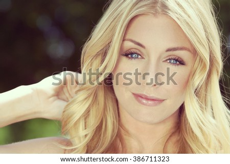 Instagram style portrait of naturally beautiful woman in her twenties with blond hair and blue eyes, shot outside in sunlight with a natural green background - stock photo