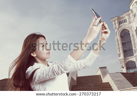 Instagram style vintage image. Young japanese women with long hair do selfie in city park afainst steps and clear blue sky with light haze, copyspace on the sky - stock photo