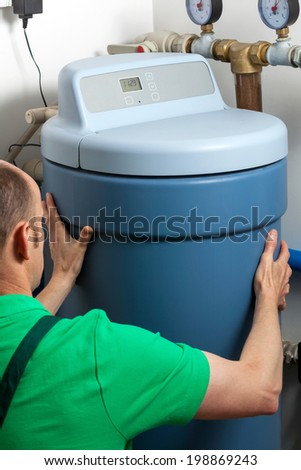 Instalation of a water softener in boiler room - stock photo