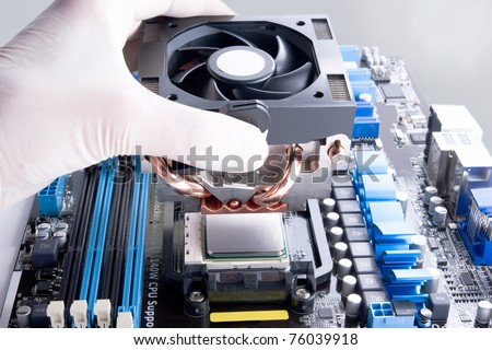 installing black cooler fan with copper tubes on computer processor - stock photo