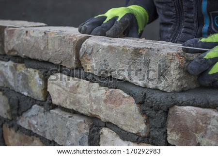 Installing brick, build a brick wall. Bricklaying foundation walls, lay bricks. - stock photo