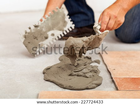 Installing ceramic floor tiles - apply the adhesive, closeup - stock photo