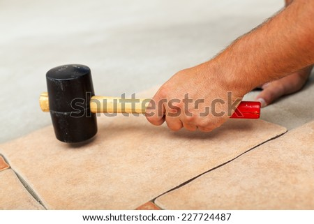 Installing ceramic floor tiles - fitting the tiles together in a plane, closeup - stock photo