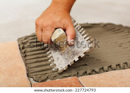 Installing ceramic floor tiles - spreading the adhesive material, closeup - stock photo