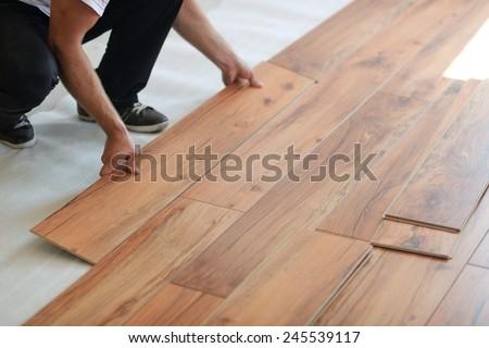 Installing laminate flooring in new home indoor - stock photo