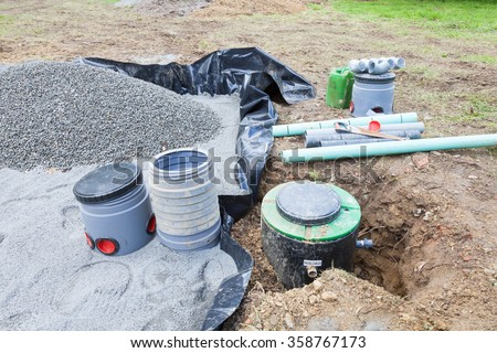 Installing the gravel filter bed and pump for a septic tank sanitation system for a residential house for the disposal of wastewater and sewage - stock photo