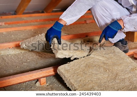 Installing thermal insulation layer - closeup on hands cutting rock wool - stock photo