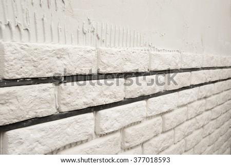 Installing white decorative bricks on the wall - stock photo