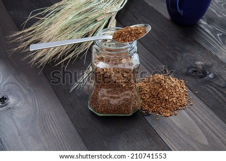 Instant coffee on a spoon that lies on a glass jar - stock photo