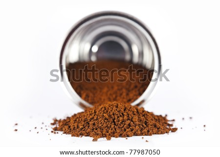 Instant coffee poured from a metal tin on a white background. - stock photo