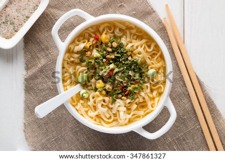 instant noodles in a white plate with vegetables and chopsticks - stock photo