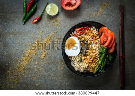 Instant noodles with spicy seasoning, vegetables and salted egg. Top view. - stock photo