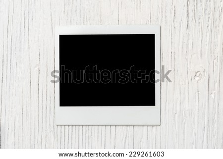 instant photo frame on wooden background - stock photo