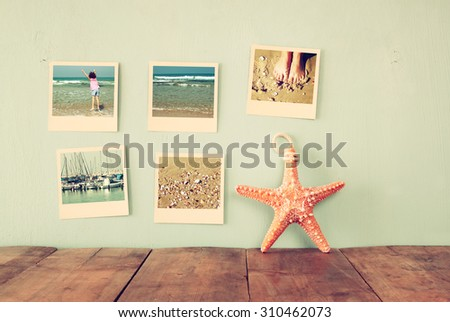 instant photos hang over wooden textured background next to decorative starfish. retro filtered image  - stock photo