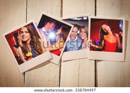 Instant photos on wooden floor against pretty brunette dancing and smiling - stock photo
