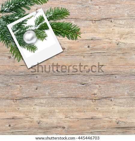 Instant picture with silver Christmas tree ball and fir branch on wooden background; Christmas greeting card; Christmas theme - stock photo