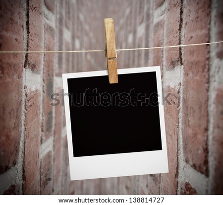 Instant print transfer hung with peg with bricks wall on the background - stock photo