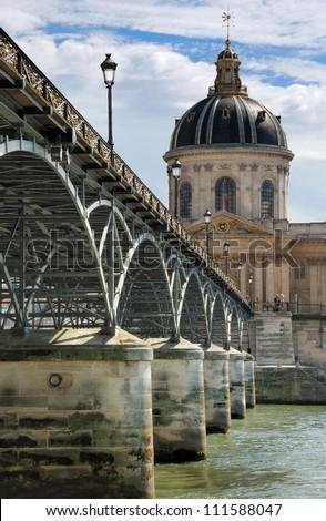 Institut de France and the Pont des Arts or Passerelle des Arts bridge across river Seine in Paris, France. - stock photo