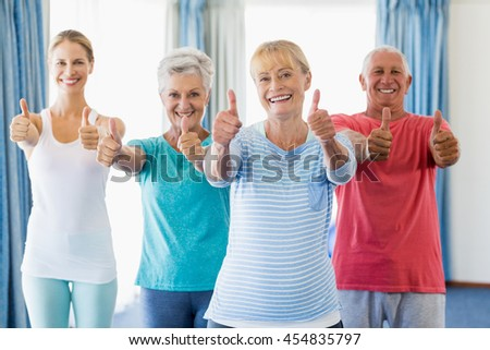 Instructor and seniors with thumbs up in a studio - stock photo