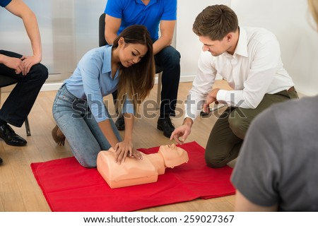 Instructor Demonstrating Cpr Chest Compression On A Dummy - stock photo