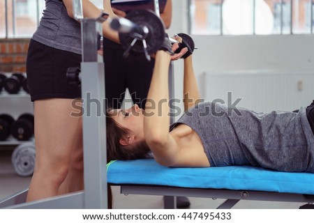 Instructor helping a young woman doing fitness training and bodybuilding lifting weights stepping forwards to secure the barbell after it has been raised on the bench - stock photo